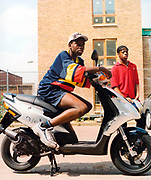 Teenage boy sitting on a silver moped outside a newly built housing complex