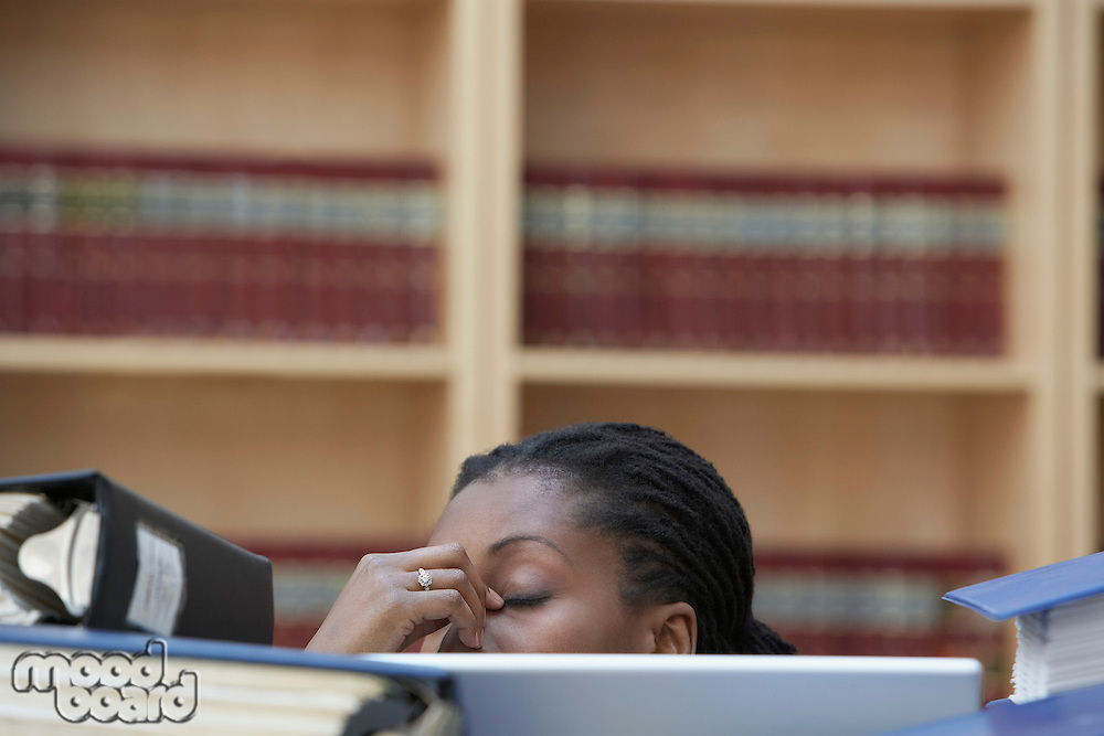 Office worker sitting behind stacks of documents in office high section