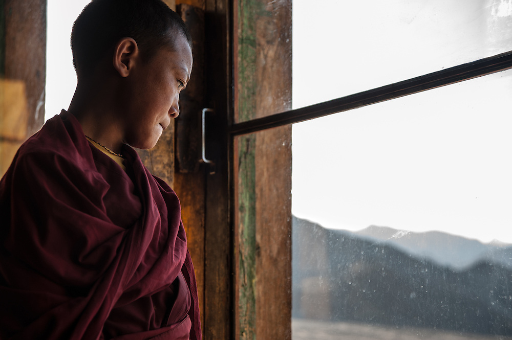 A young monk looks out the window at Thiksey Monastery in Ladakh