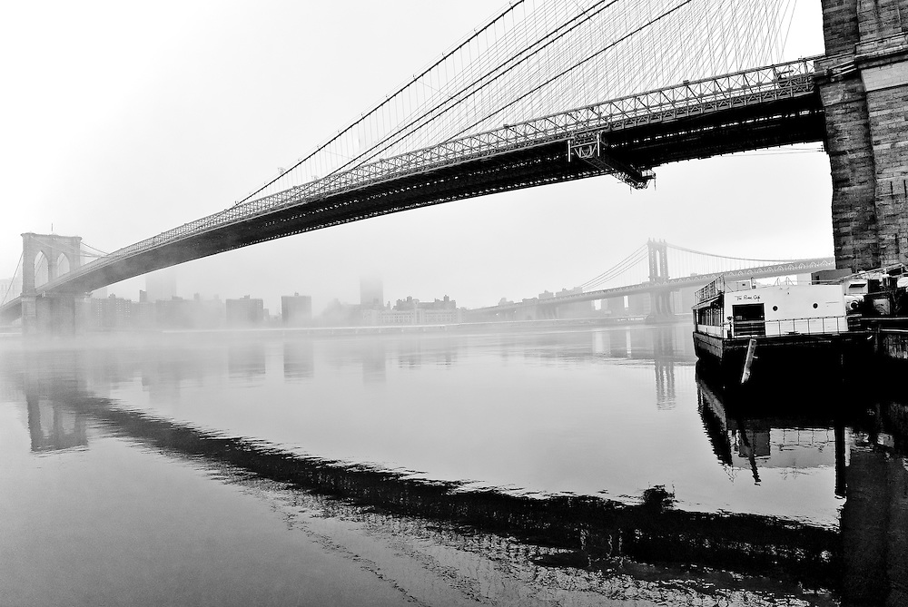 The Brooklyn Bridge and the Manhattan Bridge in the fog, on the bank of the East River, Brooklyn, New York.