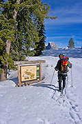 Backcountry skier looking at trail sign at Glacier Point, Yosemite National Park, California