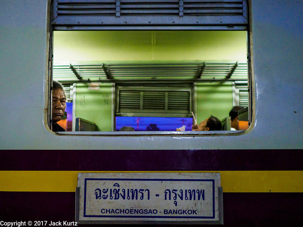 31 MAY 2017 - CHACHOENGSAO, THAILAND: A passenger looks out his window on the 5.45AM train, the first train of the day, at the train station in Chachoengsao, a provincial town about 50 miles and about an hour by train from Bangkok. The train from Chachoengsao to Bangkok takes a little over an hour but traffic on the roads is so bad that the same drive can take two to three hours. Thousands of Thais live outside of Bangkok and commute into the city for work on trains, busses and boats.       PHOTO BY JACK KURTZ