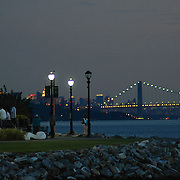 The sun has set on this jazz combo's musical performance on the Hudson River at Yonkers' Sculpture Park. Lights from New York City and George Washington Bridge twinkle in the background twilight.