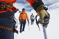 Hikers using walking sticks in snowy mountains mid section on front man