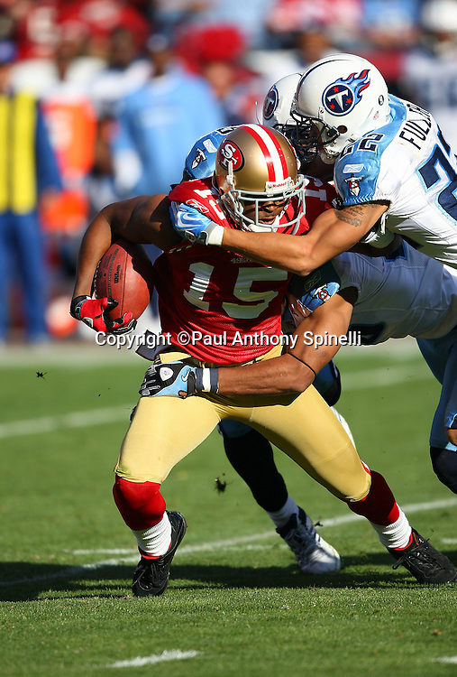 San Francisco 49ers wide receiver Michael Crabtree (15) gets tackled by Tennessee Titans safety Vincent Fuller (22) during the NFL football game against the Tennessee Titans, November 8, 2009 in San Francisco, California. The Titans won the game 34-27. (©Paul Anthony Spinelli)