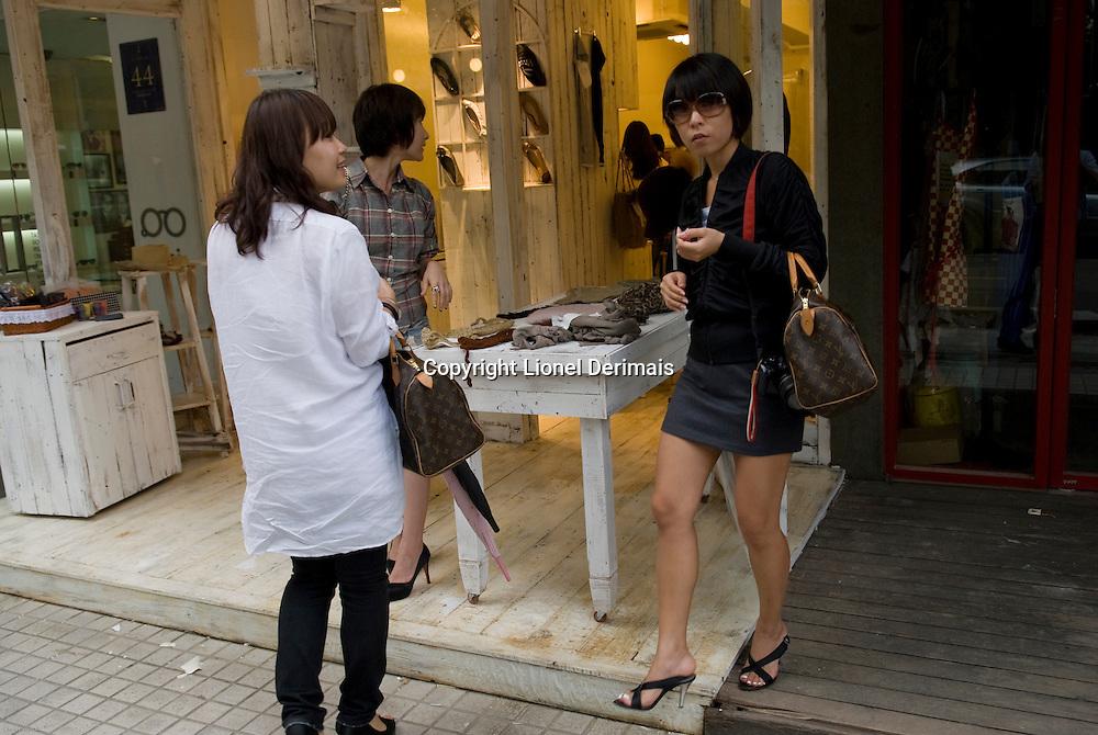 Jeunes femmes faisant du shopping dans le quartier de Sinsa, Seoul, South Korea.<br /> <br /> Young women shopping in Sinsa district, Seoul, South Korea.