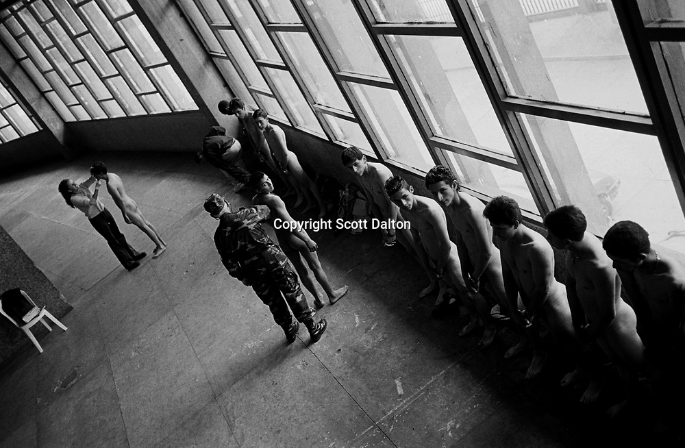 A soldier reviews young draftees waiting for their military medical exam at a Bogotá auditorium. (Photo/Scott Dalton)