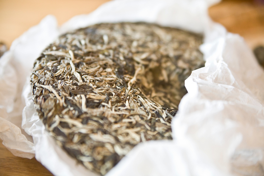 A disc of white tea pu-erh with the parchment paper partially unwrapped.