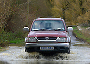 © Licensed to London News Pictures. 22/11/2012. Oxfordshire, UK A car drives through floodwater in Somerton. Flooding in Oxfordshire today 22 November 2012. Heavy rain across large parts of the South West of the country has caused widespread flooding. Photo credit : Stephen Simpson/LNP