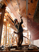 Evelyn Ansel, an apprentice shipwright at the Mystic Seaport's H.B. duPont Preservation Shipyard, caulks planks below the waterline of the whaleship Charles W. Morgan Friday, April 12, 2013.  The Morgan, the last remaining wooden whaling ship remaining and the oldest American commercial vessel still in existence as well as a National Historic Landmark, is slated to be re-launched on July 21st this summer and embark on its 38th voyage, a tour of historic New England ports in the spring of 2014. (Sean D. Elliot/The Day)