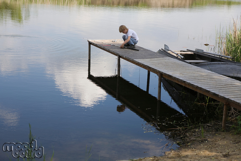 Boy sitting at end of jetty by lake