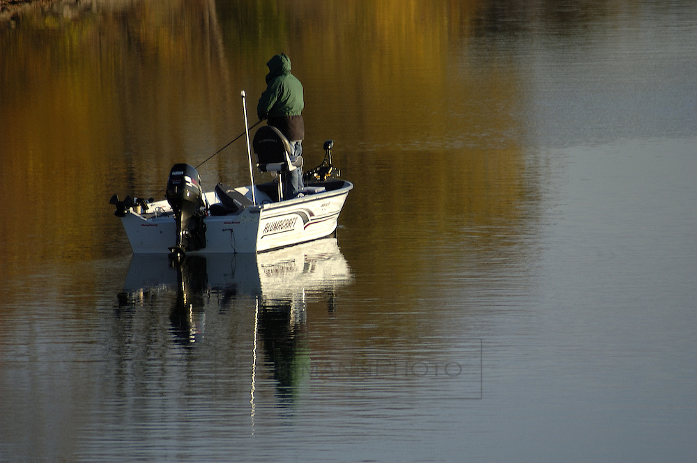 Man fishing in a motorized fishing boat on a lake