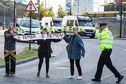London, UK. 7 September, 2019. A Metropolitan Police officer approaches activists holding a banner reading 'O Yemen' in the road as a vehicle approaches ExCel London on the sixth day of Stop The Arms Fair protests against DSEI, the world's largest arms fair. The sixth day of protests was billed as a Festival of Resistance and included performances, entertainment for children and workshops as well as activities intended to disrupt deliveries to ExCel London for the arms fair.