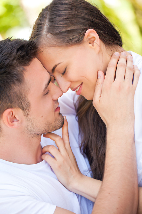 Smiling young couple embracing and enjoying in their love on sunny morning outdoors.
