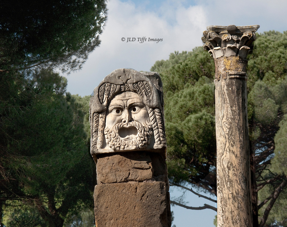 Ostia Antica.  Closeup of a theatrical mask carved in stone; Corinthian pillar and umbrella pines behind.  Mask's mouth is wide open as though screaming.