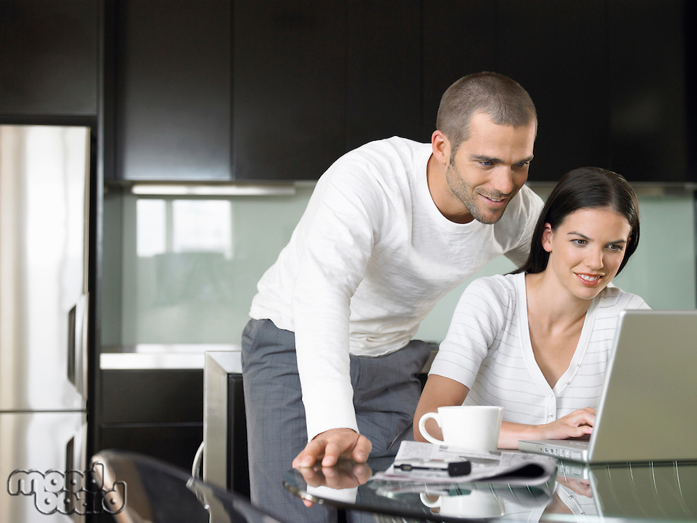 Couple looking at lap top in modern kitchen