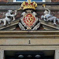 Pediment above Ministry of Finance Entrance in Copenhagen, Denmark<br /> This pediment with the Danish crown, the monogram of King Frederik IV and two cherubs blowing horns caught my eye. The address of Christiansborg Slotsplads 1 is the entry to Denmark's Ministry of Finance. They are an arm of the government that analyzes the country's economic and financial environment and support decisions regarding the budget and policy formation.  Reporting to it are four government agencies.