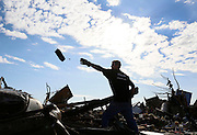 Jon Booth throws debris from his mother's tornado-destroyed home across the street from the Plaza Towers elementary school in Moore, Oklahoma May 22, 2013. A massive tornado tore through a suburb of Oklahoma City, wiping out whole blocks and killing at least 24.   REUTERS/Rick Wilking (UNITED STATES)
