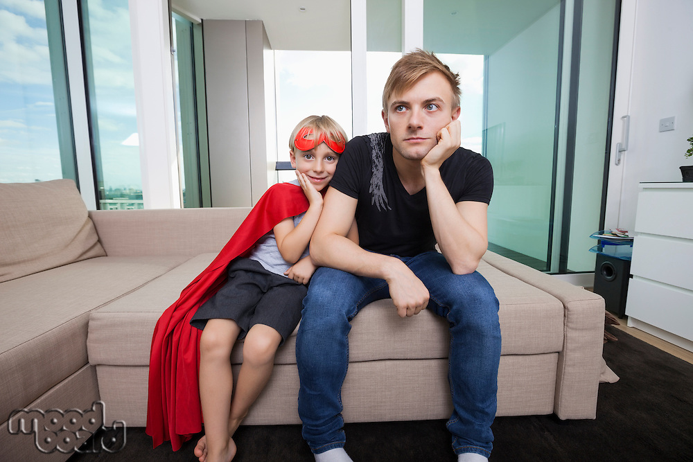 Portrait of smiling boy dressed in superhero costume sitting with sad father on sofa bed at home