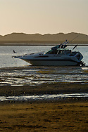 Anchored boat stuck in tidal mud flat at low tide in Morro Bay, California