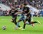 LAFC Lee Nguyen (24) and Steven Beitashour (3) defend  against Sporting KC forward Johnny Russell (7) during a MLS soccer match against the Sporting KC in Los Angeles, Sunday, March 3, 2019. LAFC defeated Sporting KC, 2-1. (Ed Ruvalcaba/Image of Sport)