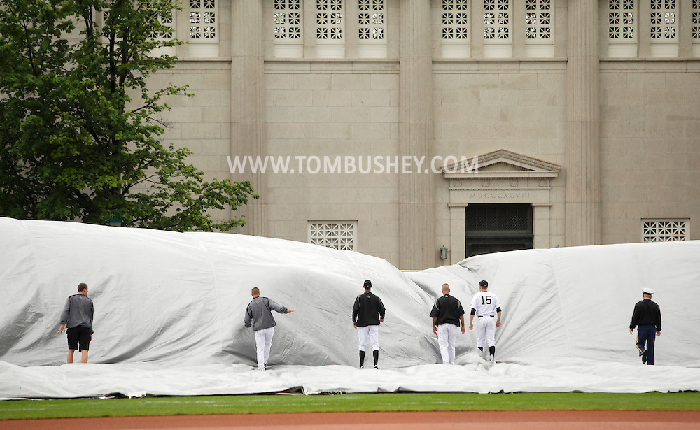 Army baseball players and coaches remove the tarp from the field before the start of the Patriot League championship game against Holy Cross at West Point on May 21, 2012.