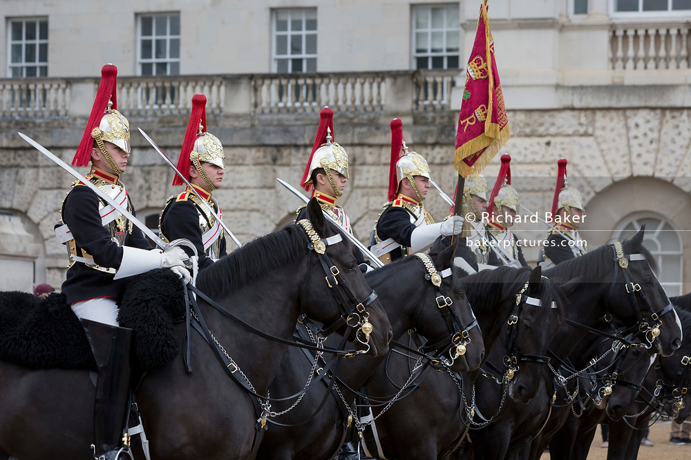 Members of the Blues and Royals (blue tunics) change guard with the Queen's Life Guard (red tunics) during the daily ceremonial in Horse Guards Parade, on 11th June 2019, in London, England. Life Guards have stood guard at Horse Guards, the official entrance to St James and Buckingham Palace, since the Restoration of King Charles II in 1660.