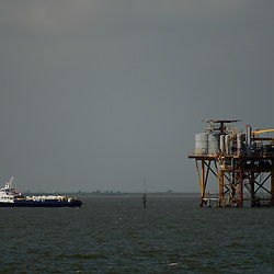 A support vessel pulls away from a production platform standing in the Gulf of Mexico off the coast of Louisiana, U.S., on Thursday, July 15, 2010. Photographer: Derick E. Hingle/Bloomberg