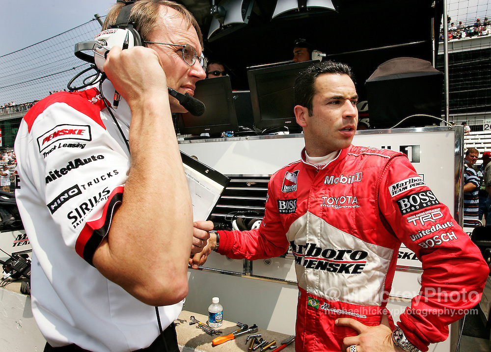 IRL driver Helio Castroneves talks with a crew member during practice for the Indy 500.