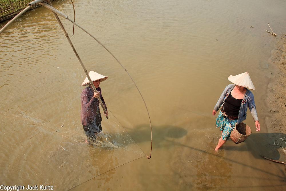 Mar. 12, 2009 -- VANG VIENG, LAOS: Women fish in their fish pond on the Nam Xong River in Vang Vieng, Laos,  Photo by Jack Kurtz