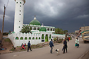 A man with a goat on a leash walks past a mosque in Narok, Kenya on an afternoon with threatening storm clouds looming.