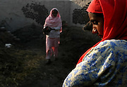 Women clean an open courtyard of their home in Khairo Dero village, in Larkana, Pakistan, on Thursday, Jan. 24, 2008. Pakistan is seeking to sustain growth in a country where the government estimates a fourth of the population lives in poverty, or on less than a dollar a day.