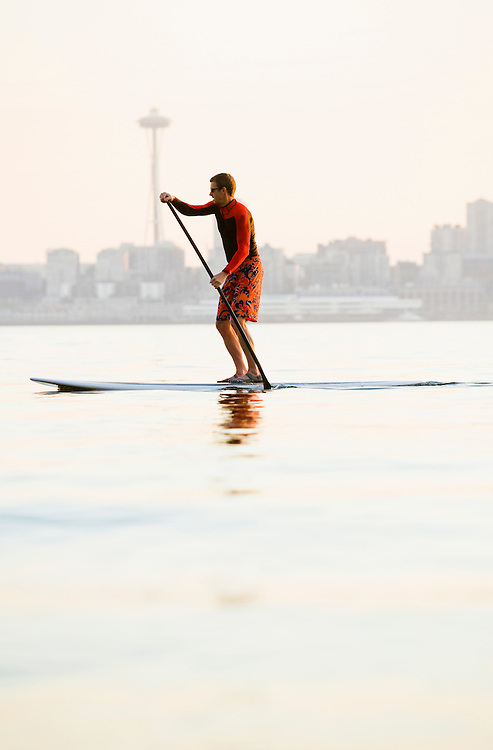 A man paddling on his stand-up paddle board on Elliott Bay with the Seattle Space Needle in the background.
