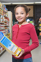 Young girl holding cereal packet