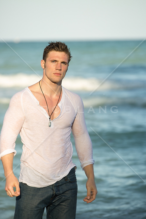 hot man in wet clothes at the beach