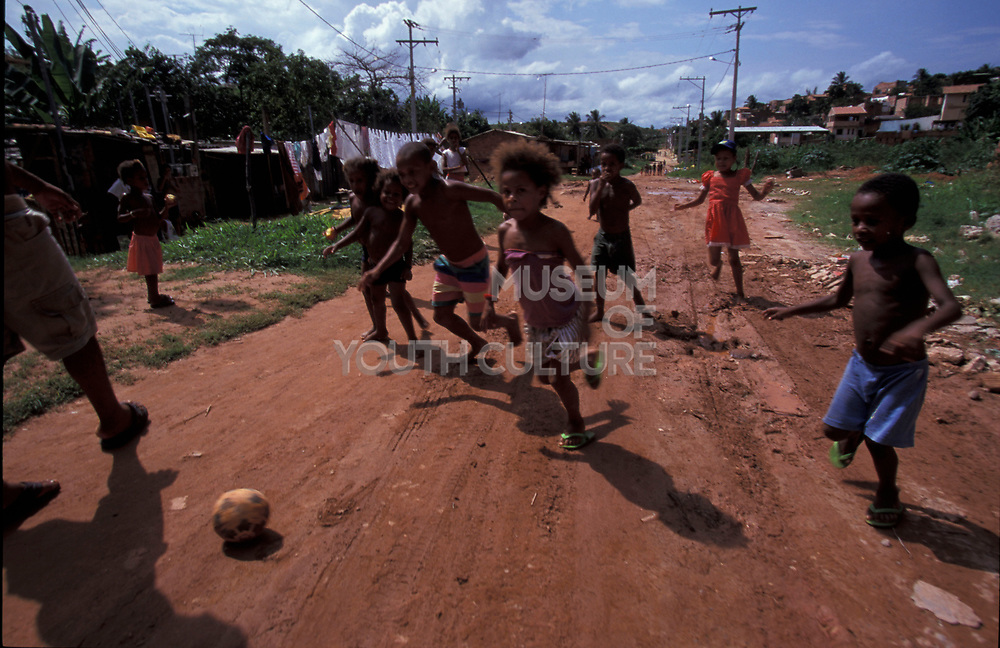 Group of kids running down a path playing football, Brazil, 2000's