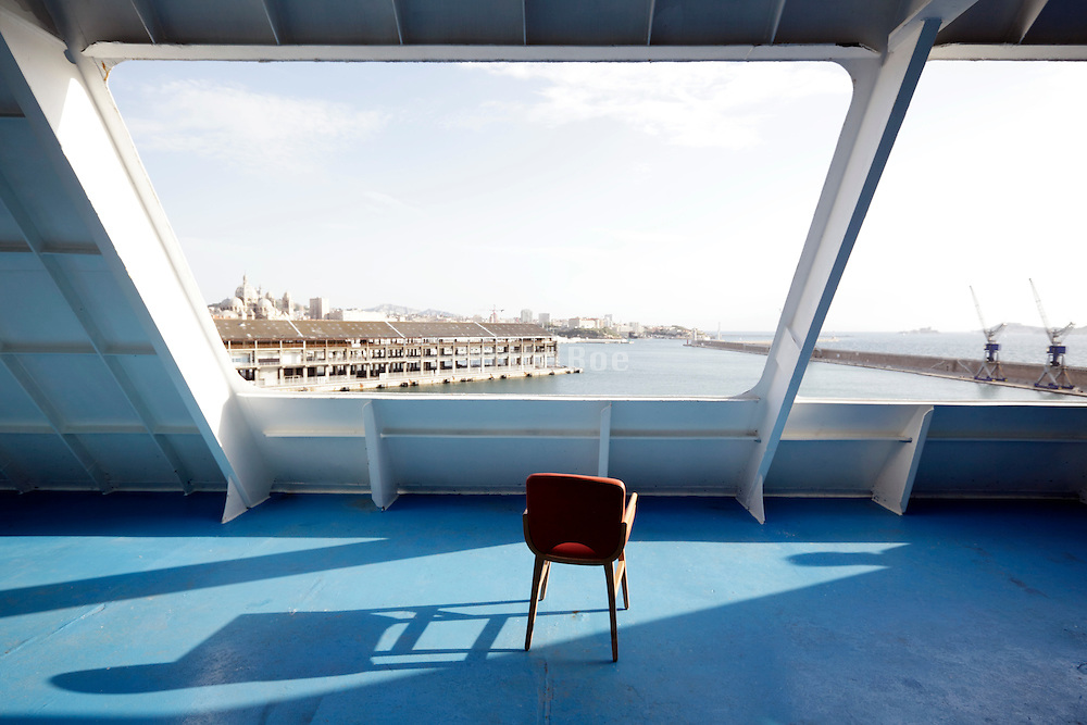 large ferry ship in Marseille harbor with one chair on the back dock