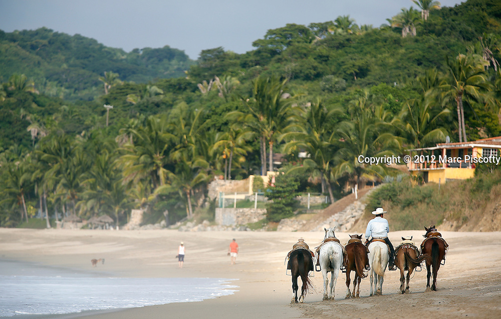 """SHOT 11/13/12 4:08:17 PM - A local rides the beach looking for tourists to rent horses for a horseback ride into the surrounding countryside in Sayulita, Mexico. Sayulita is a small fishing village about 25 miles north of downtown Puerto Vallarta in the state of Nayarit, Mexico, with a population of approximately 4,000. Known for its consistent river mouth surf break, roving surfers """"discovered"""" Sayulita in the late 60's with the construction of Mexican Highway 200. In recent years, it has become increasingly popular as a holiday and vacation destination, especially with surfing enthusiasts and American and Canadian tourists. .(Photo by Marc Piscotty / © 2012)"""