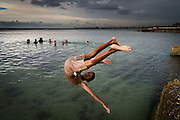 A boy flips into the water at the Playa Jaimanitas on the western edge of Havana, Cuba.
