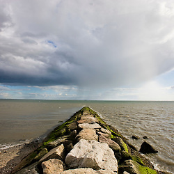 Rainshowers in the distance as seen from a breakwater on Long Beach in Stratford, Connecticut.  Adjacent to the Great Meadows Unit of McKinney National Wildlife Refuge.