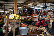 Campo de Fiori outdoor market, Rome. A red bicycle with baskets is parked beside tables with basket of lemons and other fruits and vegetables, a wreath of garlic. People shop beneath tents and umbrellas.