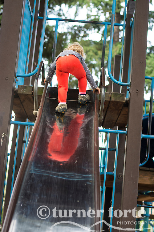 Toddler girl climbs to the top of a slide at playground in Portland, Oregon.
