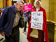 "04 MAY 2017 - ST. PAUL, MN: A woman dressed as a handmaid (from the novel and Hulu series ""A Handmaid's Tale"") talks to a man walking past the Minnesota State Senate chamber. About 50 people came to a protest to urge Minnesota State Senators to vote against two bills supported by the Republican party that would restrict access to women's health care in Minnesota. The protest was organized by  NARAL Pro-Choice Minnesota, NCJW Minnesota, and Planned Parenthood Minnesota. The Senate passed the bills but Minnesota's Democratic governor is expected to veto the legislation when it reaches his desk.     PHOTO BY JACK KURTZ"