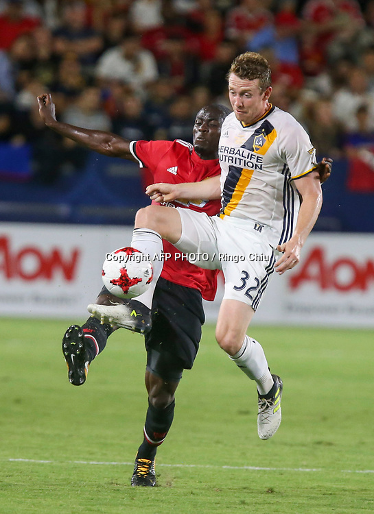 Manchester United Eric Bailly, left, and Los Angeles Galaxy  Jack McBean battle for the ball during the second half of a national friendly soccer game at StubHub Center on July 15, 2017 in Carson, California. The Manchester United won 5-2. AFP PHOTO / Ringo Chiu