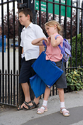 Brother and sister waiting at the school gates,