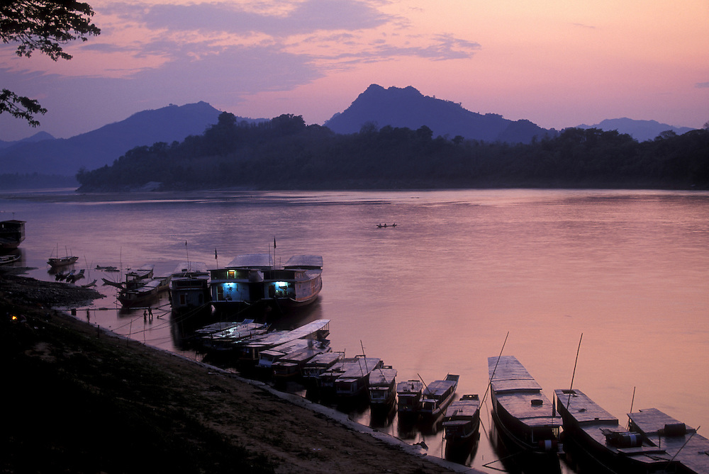 Asia, Laos, Luang Prabang,  Wooden freight and passenger boats line banks of Mekong River at dusk