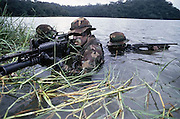 15 Sep 1994, Panama --- On a special operation with a SBU (Small Boat Unit), a Navy SEAL team is armed with a M16A3 rifle, a M209 grenade launcher, and a shotgun. The group approaches the rivershore. --- Image by © Leif Skoogfors