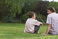 Father and son (10-12) sitting on lawn and talking