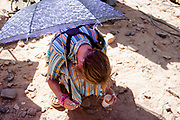 Lady crouched on the floor with purple umbrella at Middle East Tek, Wadi Rum, Jordan, 2008