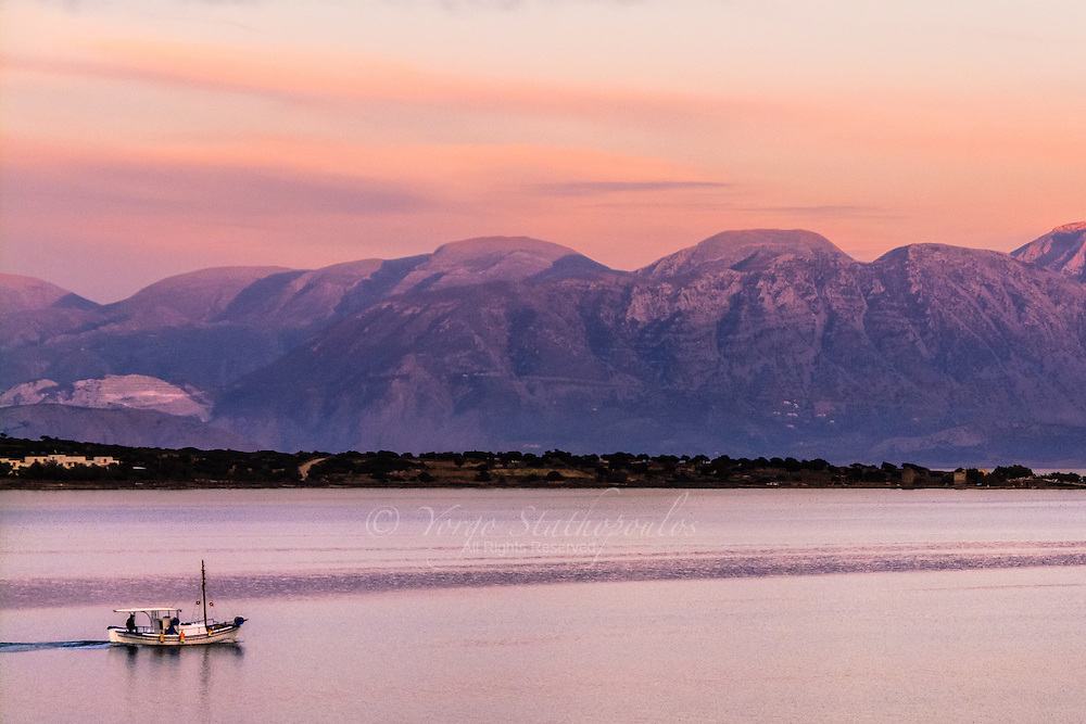 Mirabello Bay, Lassithi Crete Greece. Kaiki (fishing boat) returning with the days catch during magic hour in Mirabello Bay. The beautiful mountains of Sitia in the background.